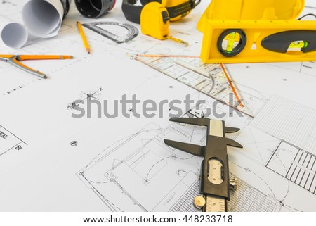 Construction plans with yellow helmet and drawing tools on blueprints - stock photo