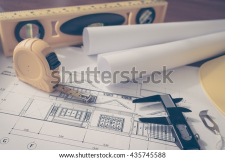Construction plans with yellow helmet and drawing tools on blueprints  ( Filtered image processed vintage effect. ) - stock photo