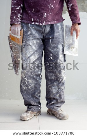 construction plastering man dirty trousers with trowel and saw in hand - stock photo