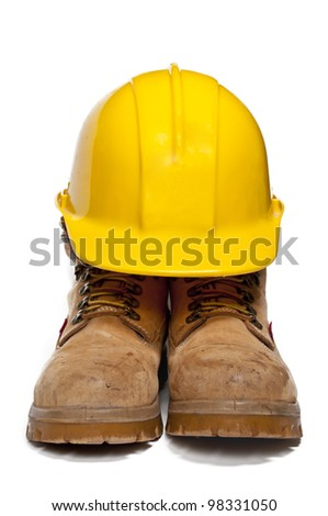 Construction PPE - Steel toe boots and a yellow hard hat - stock photo