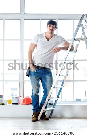 Construction, repair and moving into an apartment. Portrait of a worker repairs in a new apartment near the ladder in an empty house - stock photo