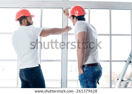 Construction, repair and moving into an apartment. Two workers make measurements of windows and repairs in a new apartment while ladder stands in an empty apartment. - stock photo