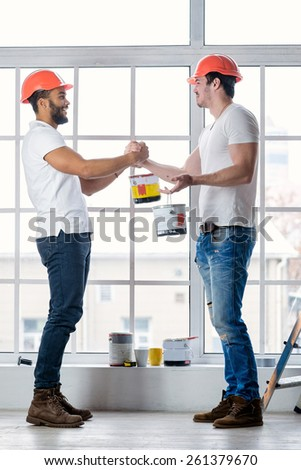 Construction, repair and moving into an apartment. Two workers wearing helmets keep the paint in the new apartment while ladder stands in an empty apartment and stand opposite each other - stock photo