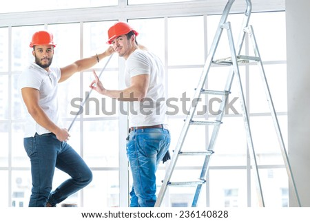 Construction, repair and moving into an apartment. Two workers wearing helmets make measurements of windows and repairs in a new apartment stairs while standing in an empty apartment and show Okay - stock photo