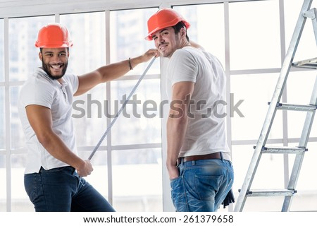 Construction, repair and moving into an apartment. Two workers wearing helmets make measurements of windows and repairs in a new apartment ladder while standing in an empty apartment. - stock photo