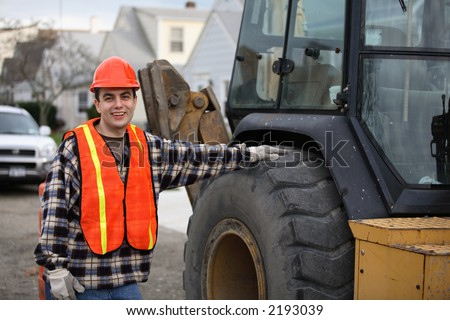Construction road worker, standing next to tractor/bulldozer/excavator, his hand on the wheel. Residential area on the background.
