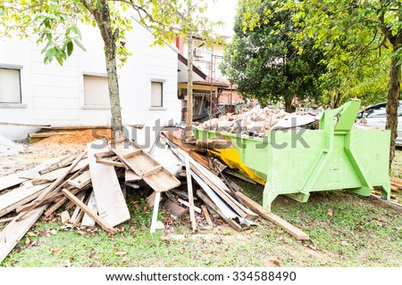Construction rubbish bin with loads at construction site, and with unfinished building in background - stock photo