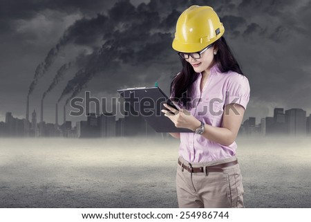 Construction safety inspector marking her checklist outdoors - stock photo