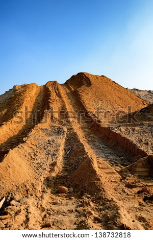 Construction sand pile with track wheel - stock photo