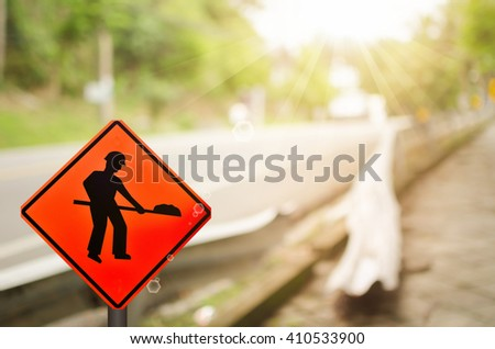 Construction sign on blur damage road abstract background. - stock photo