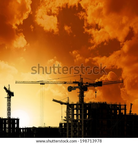 Construction silhouette with cranes and workers against orange sky - stock photo
