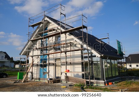 Construction site Construction site with a dwelling house under a blue sky - stock photo