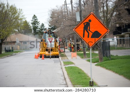 Construction site in city: Bright orange traffic sign warns of construction ahead with construction equipment in the background. - stock photo