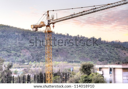 Construction site in the middle of the city. In the foreground a yellow crane