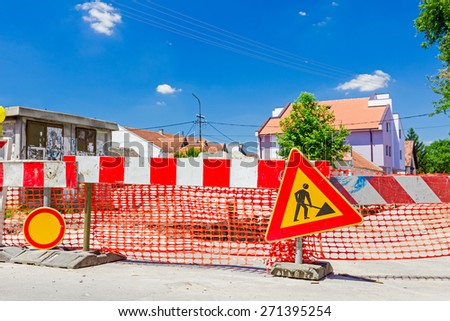 Construction site is protected by several signs and orange fence for safety. - stock photo