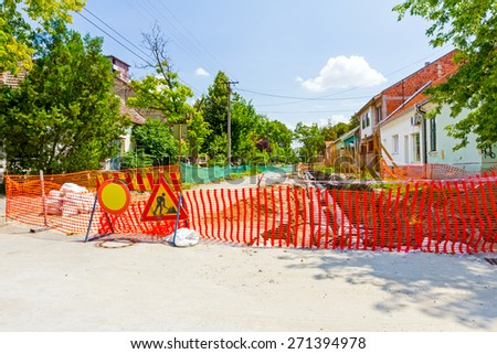 Construction site is protected by several traffic signs and orange fence for safety. - stock photo