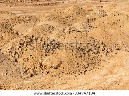 Construction site mounds of dirt and rock. Red orange brown rust color soil.