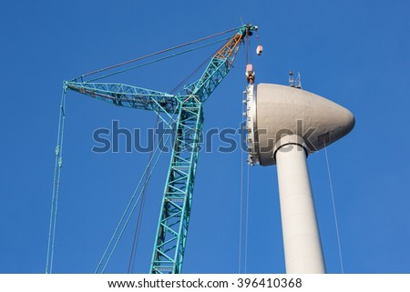 Construction site new wind turbine with hoisting of rotor house - stock photo