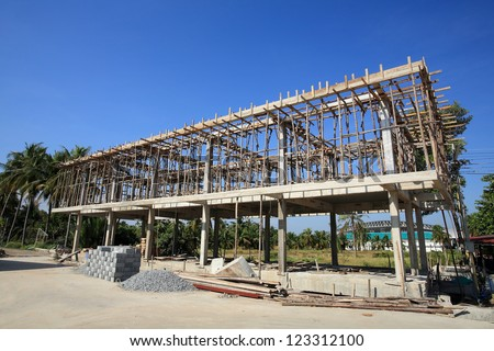 construction site of concrete building with wooden frames against blue sky - stock photo