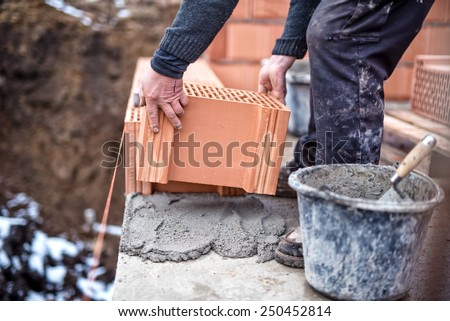 Construction site of new house, worker building the brick wall with trowel, cement and mortar - stock photo