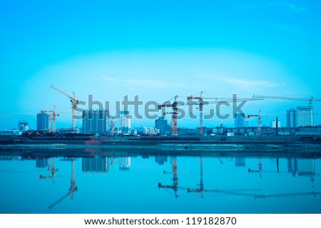construction site reflection in the river,developing city background - stock photo