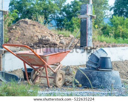 Construction site with Cement cart wheels and bucket.