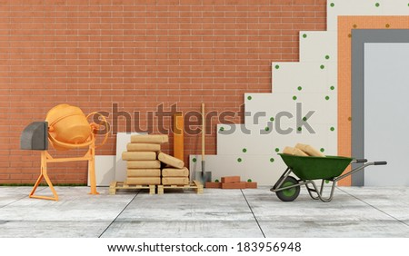 Construction site with concrete mixer, wheelbarrow, bags of cement and panels for thermal insulation of a facade - rendering - stock photo
