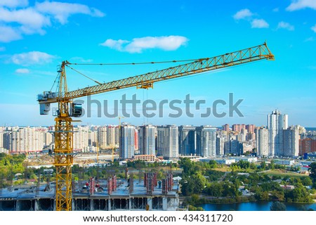 Construction site with crane and workers in progress