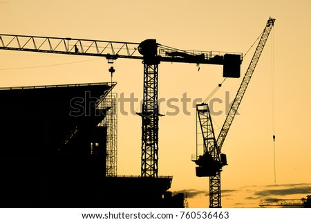 Construction site with crane at sunset.silhouette of construction tower crane group with sunset sky background