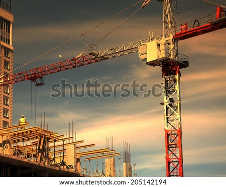 construction site with crane on sunset sky background - stock photo