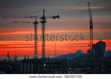 Construction site with cranes against a red sky in the light of the rising sun, sunrise