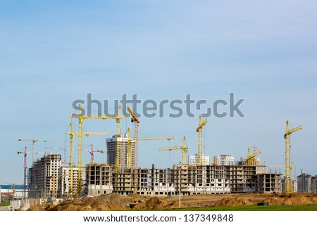 Construction site with cranes and buildings under construction - stock photo