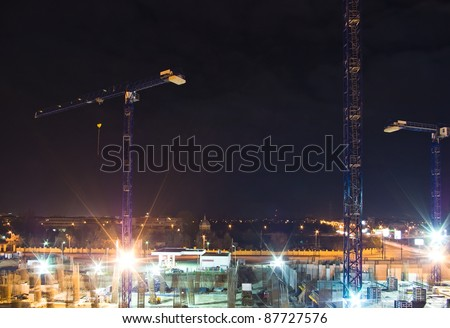 construction site with cranes and lights at night - stock photo