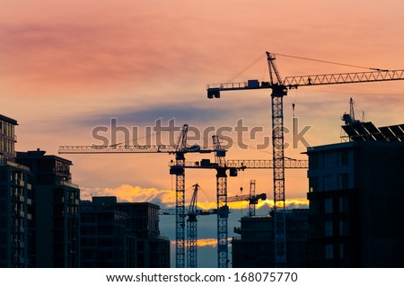 Construction site with cranes at sunset, sunrise, dawn time with the cranes as a silhouette. Vancouver, Canada. - stock photo