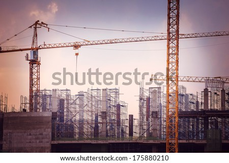 Construction site with cranes on sky background, retro tone image - stock photo