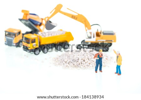 Construction site with miniature workers, excavator, dump truck and cement mixer close up  - stock photo