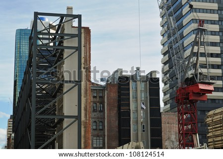 Construction site with old building facade support and crane on construction site, old walls inside with modern building around in Melbourne, Australia - stock photo