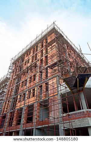 Construction site with scaffolding around new building. - stock photo