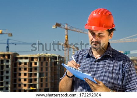 Construction site worker looking at paper,controls quality of the construction - stock photo