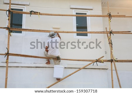 Construction site: worker on wooden scaffold painting house by roller - stock photo