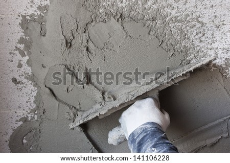 Construction site - Worker performs internal plaster - stock photo