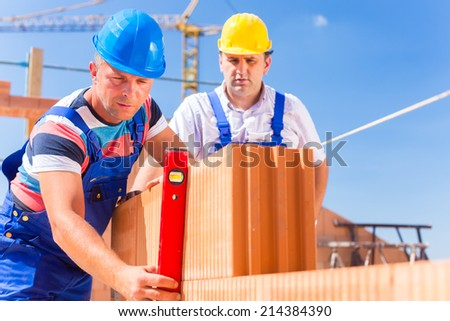 Construction site workers or bricklayer with helmets controlling building walls with a bubble level  - stock photo