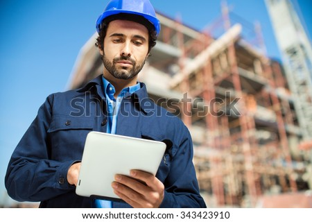 Construction specialist using a tablet computer - stock photo