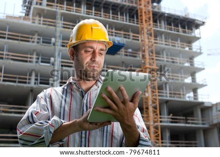 Construction specialist using a tablet computer. At a construction site. - stock photo