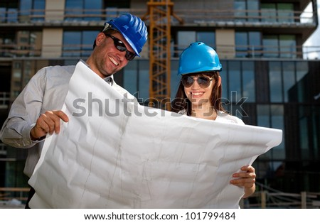Construction specialists reviewing blueprints at a construction site. - stock photo