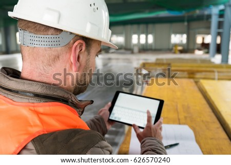 Construction supervisor checks the interior of a new warehouse being constructed with digital tablet in his hand, wearing a safety helmet and vest