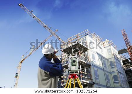 construction surveyor, engineer with measuring instrument, building industry in background - stock photo