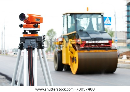 Construction surveyor equipment theodolite level tool during asphalt paving works with compactor roller at background - stock photo