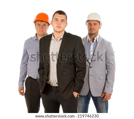 Construction team posing for the camera with a young man in a suit flanked by two men in hardhats, isolated on white