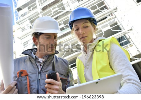 Construction team working on building site - stock photo
